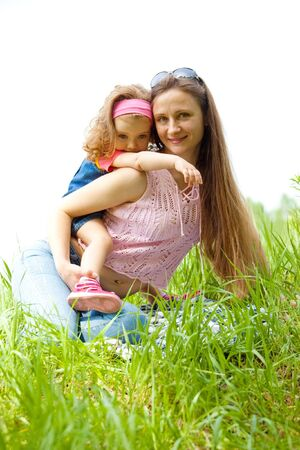 Mother and her sweet curly daughter on the meadow photo