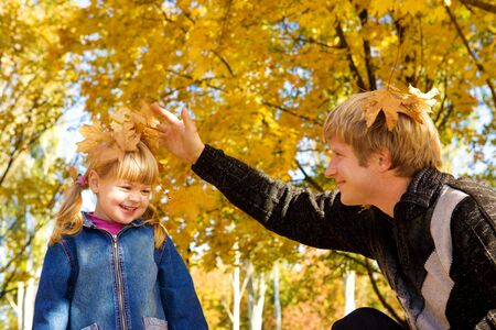Dad and daughter playing with autumn leaves photo