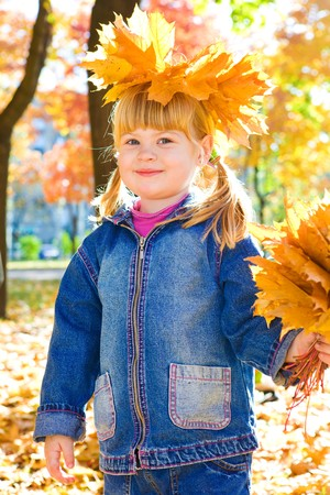 Preschool girl in casual clothing with golden leaves bunch photo