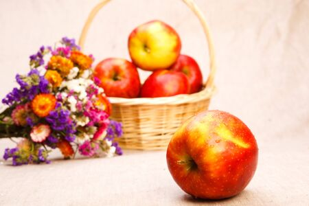 Apples in wicker basket with wildflowers beside, on textile background Stock Photo - 7640838
