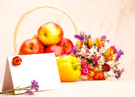 Blank greeting card with flowers and seasonal fruit and vegetables behind photo