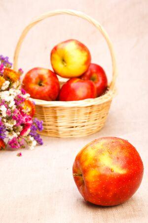 Ripe red apples in wicker basket photo