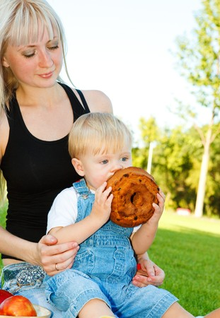 Young mother with baby son eating cake photo
