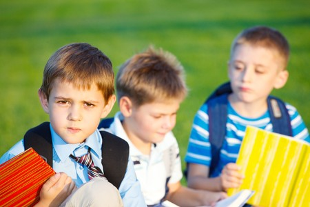 Boys with books sitting in park photo
