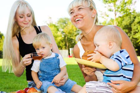 Happy mothers and their babies eating in the outdoors photo