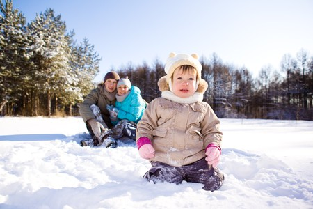 Winter toddler and her parents in a park photo