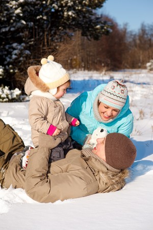Happy attractive family playing on snow photo