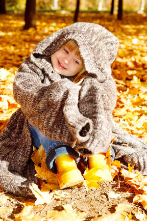 Sweet preschool girl sitting in autumn park photo