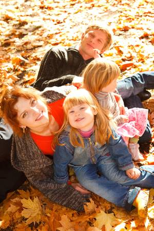 Family on autumn leaves photo