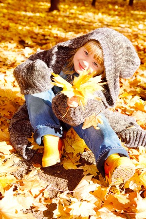 Kid with autumn leaves in hand photo