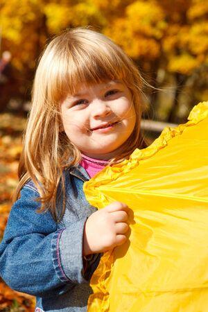 Playful girl with yellow umbrella photo