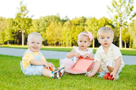 Three toddlers sitting on grass photo