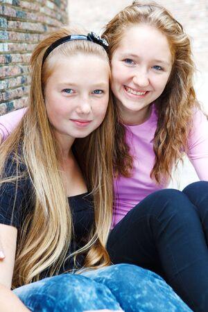 Two cute teenage friends embracing photo