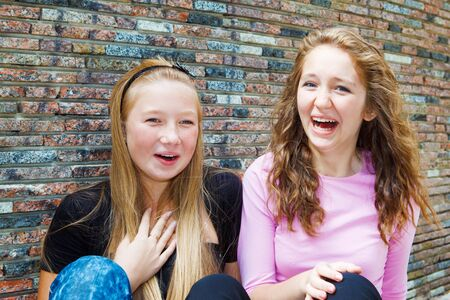 giggling: Two teenage girls laughing with surprise Stock Photo