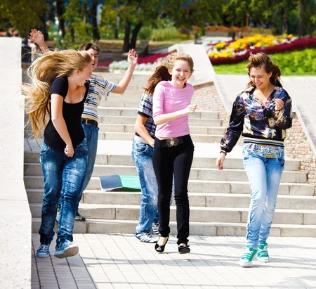 Happy teenagers running, books on stairway photo