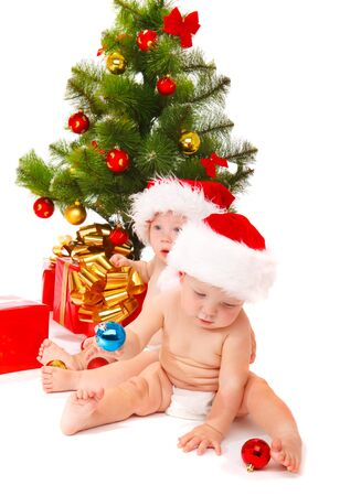 Babies in red hats playing with Christmas decoration photo