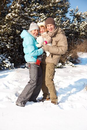 Happy attractive family in a snowy park photo