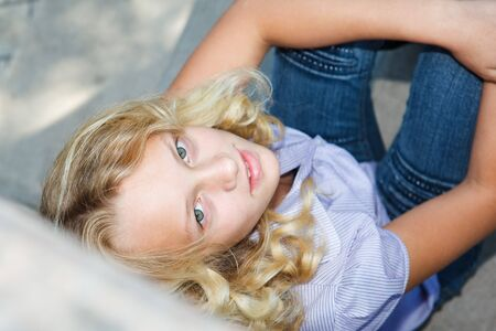Teenage girl sits on stairs and looks up photo