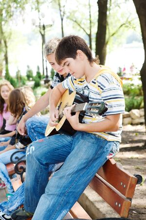 Guys with guitar, teenage girls in the background photo