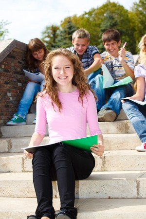 Lovely Teenage students sitting on stairway photo