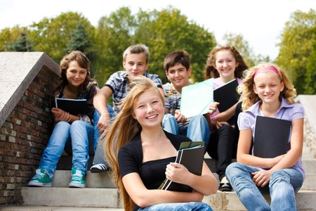 highschool: Attractive teenagers with books laughing Stock Photo