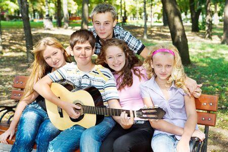 Teens playing guitar and singing photo