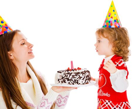 Mother giving her little daughter birthday cake photo