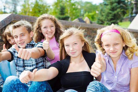 schoolchild: Happy teenagers showing thumb up