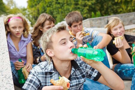 soda bottle: Teens with  sandwiches and soda water