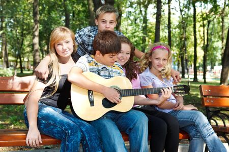 Teenagers in park playing guitar and singing Stock Photo - 7872210