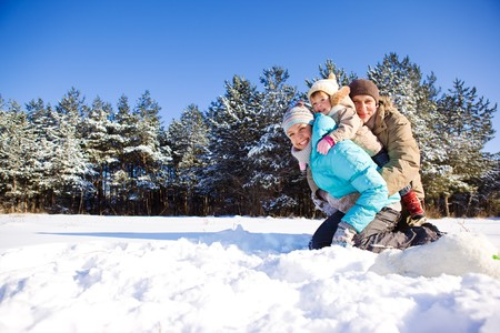 winter day: Toddler girl and her parents in a snowy park