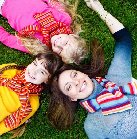 Mother and daughters lying on grass photo