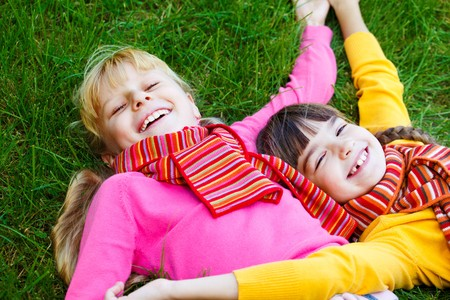 Girls in bright clothes lying on grass photo