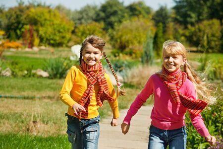 Two girls running in the garden photo