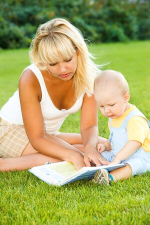 Mother and son in the backyard, reading photo