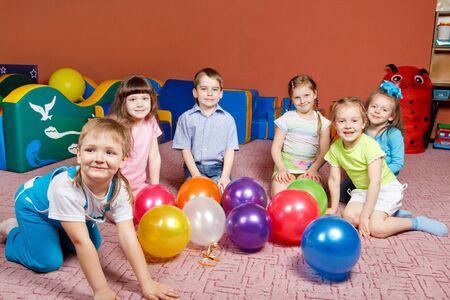 A group of preschool kids in kindergarten with balloons on the floor photo