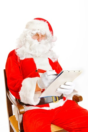 Santa Claus making notes in the wish list photo