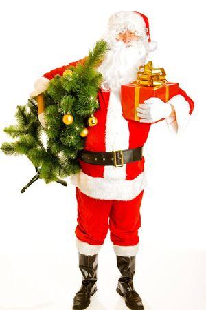 Santa Claus carrying Christmas tree and a present box photo