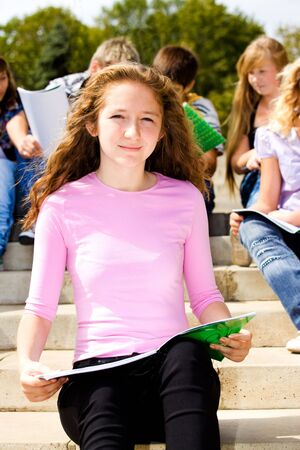 Female student sitting with book in hands, her friends behind photo