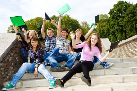 man holding book: Happy excited teens  Stock Photo