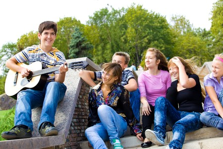 teenage guy: Cute teenage guy playing guitar for his friends