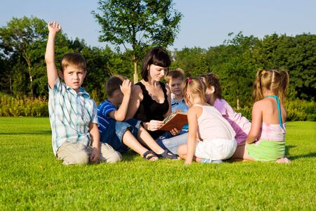 A young woman reading book to her preschool students Stock Photo - 7872223
