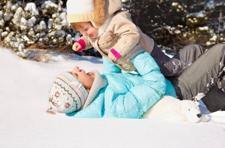 Mother and toddler playing in snow photo