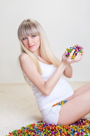 Beautiful pregnant woman with sweets in hands photo