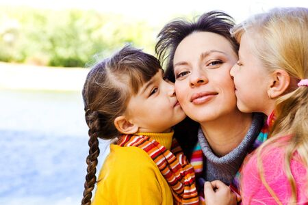 Kids kissing their happy mother photo