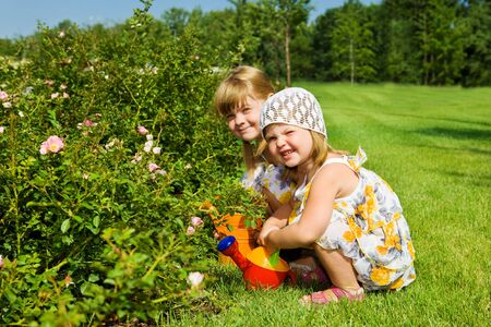 Two sweet kids watering flowers in the garden Stock Photo - 7955219