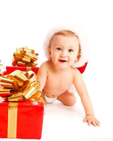 Joyful kid crawling beside Christmas present boxes photo