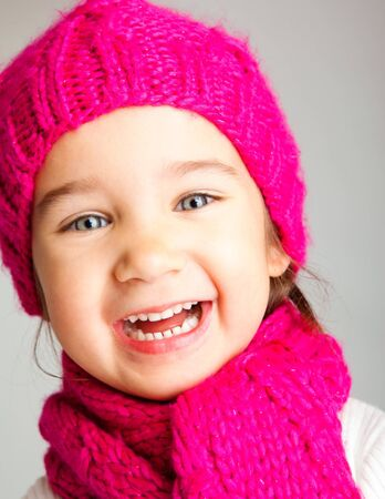 Excited preschool girl in knitted hat and scarf photo