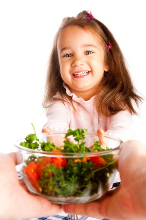 Preschool girl taking bowl with vegetable salad photo