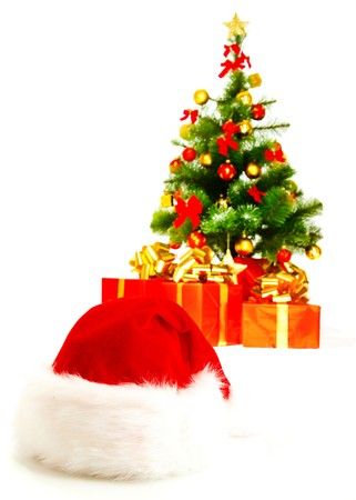 Santa hat in front and Christmas tree with present boxes photo